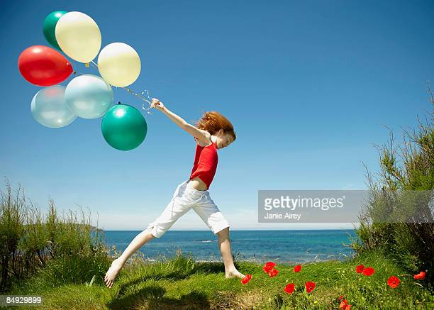 Young girl running with balloons