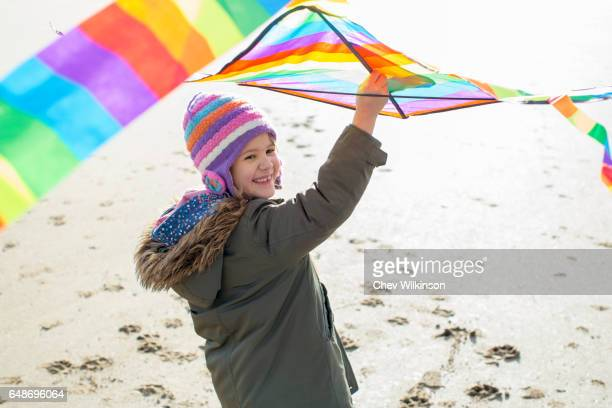 Young girl running with kite on a beach