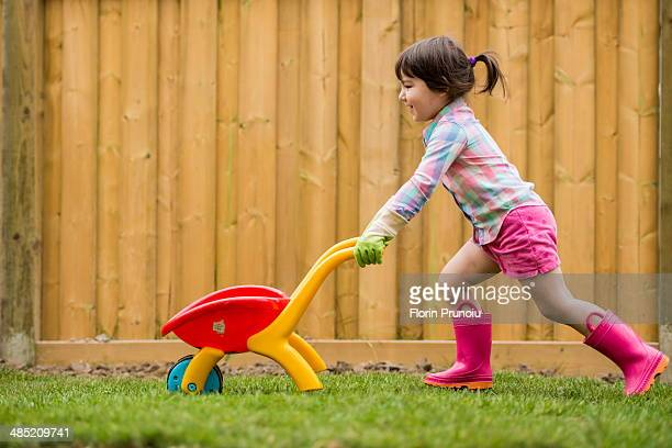 Young girl running with toy wheelbarrow in the garden