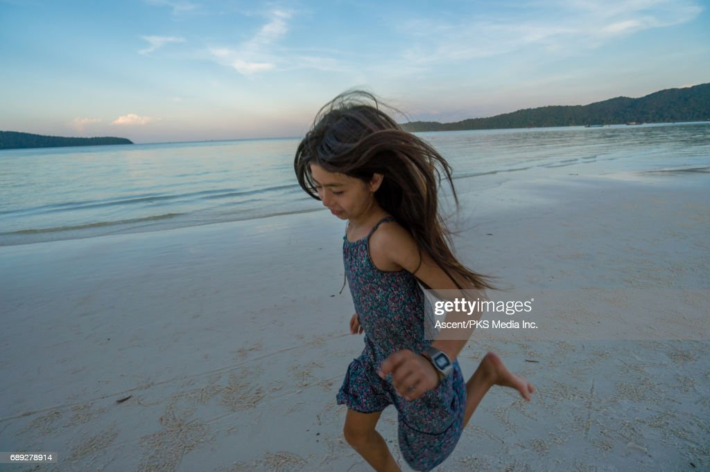 Young girl runs along beach in evening light : Stock Photo