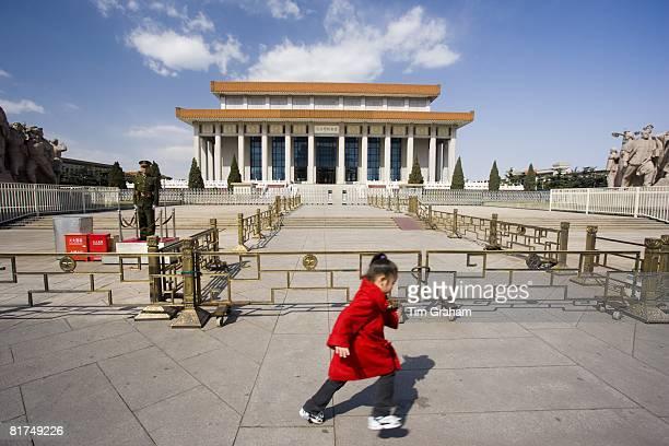Young girl runs past a soldier outside Mao's Mausoleum Tian'an Men Square Beijing China