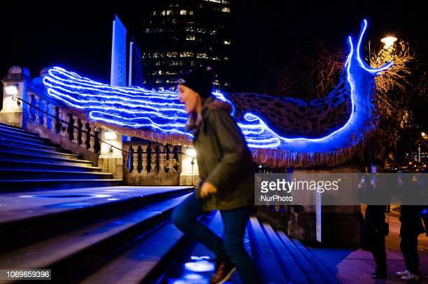 A young girl runs up the steps of the Tate Britain art gallery past artist Monster Chetwynd's giant illuminated slugs installation in London England...