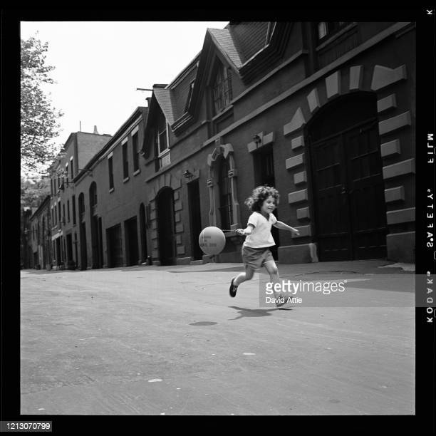 A young girl runs with a balloon on Love Lane in Brooklyn Heights in March 1958 in New York City New York