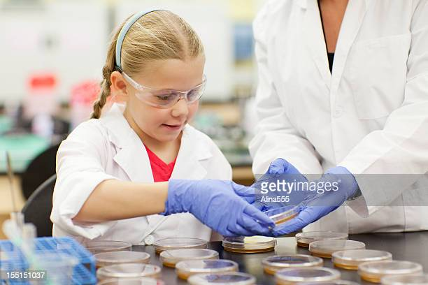 Young girl scientist and a teacher in science lab