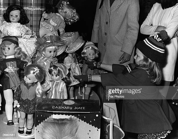 A young girl seen here choosing her Christmas present from the huge array of dolls on offer at Hamleys toy shop