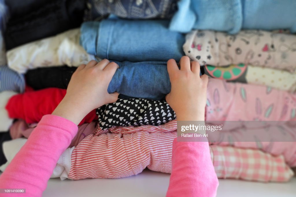POV Young Girl Selecting Clothing From a Drawer Full of Organized Young Girl Clothing : Stock Photo