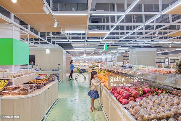 Young girl selecting fruit in supermarket