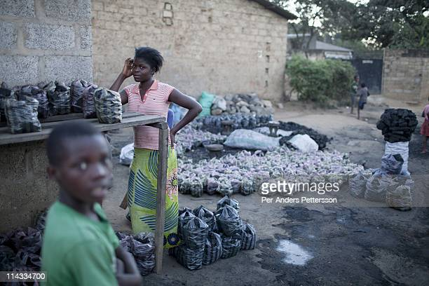 A young girl sells charcoal in a small market on June 14 2010 in central Lusaka Zambia Many people in Zambia uses charcoal for cooking Cook stoves...