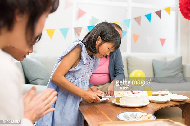 Young girl serving birthday cake