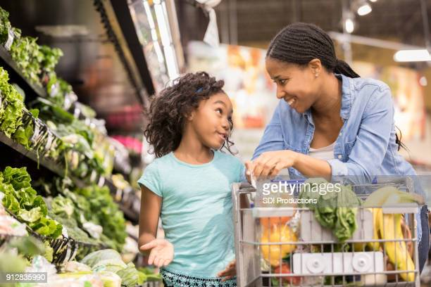 young girl shops with her mom - american influenced stock photos and pictures