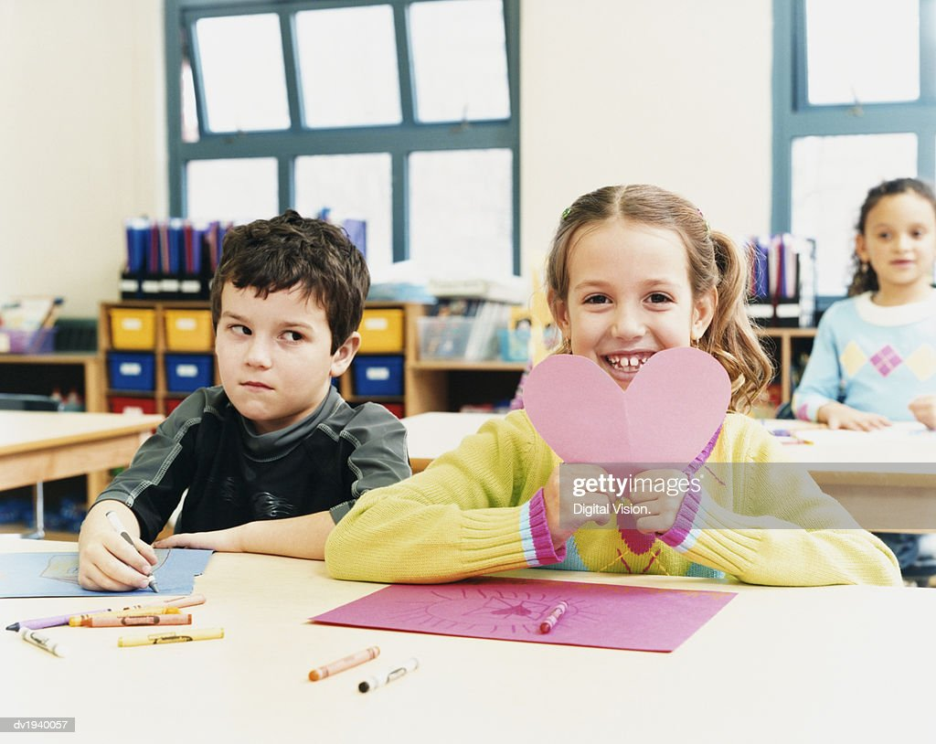 Young Girl Showing a Valentines Card She Made in Classroom as a Schoolboy Looks Sideways at Her Embarrassed : Stock Photo