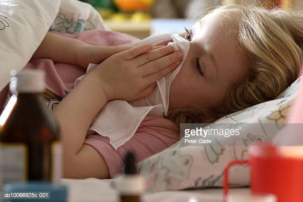 Young girl (4-5 years) sick in bed with medicine