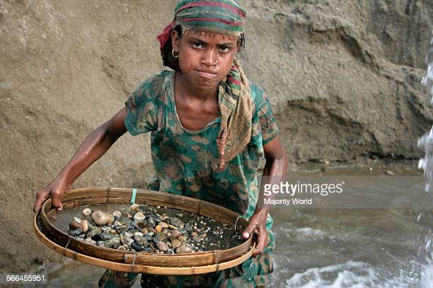 A young girl sifts stones and pebbles from sand with a bamboo strainer at a stone quarry on the bank of Dauki river in Sylhet Bangladesh January 18...