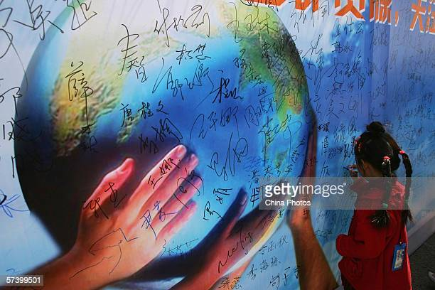 A young girl signs her name on a billboard during an activity to mark World Earth Day April 22 2006 in Beijing China China marked the 37th World...
