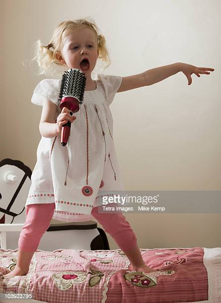 young girl singing on her bed - baby girls stock pictures, royalty-free photos & images