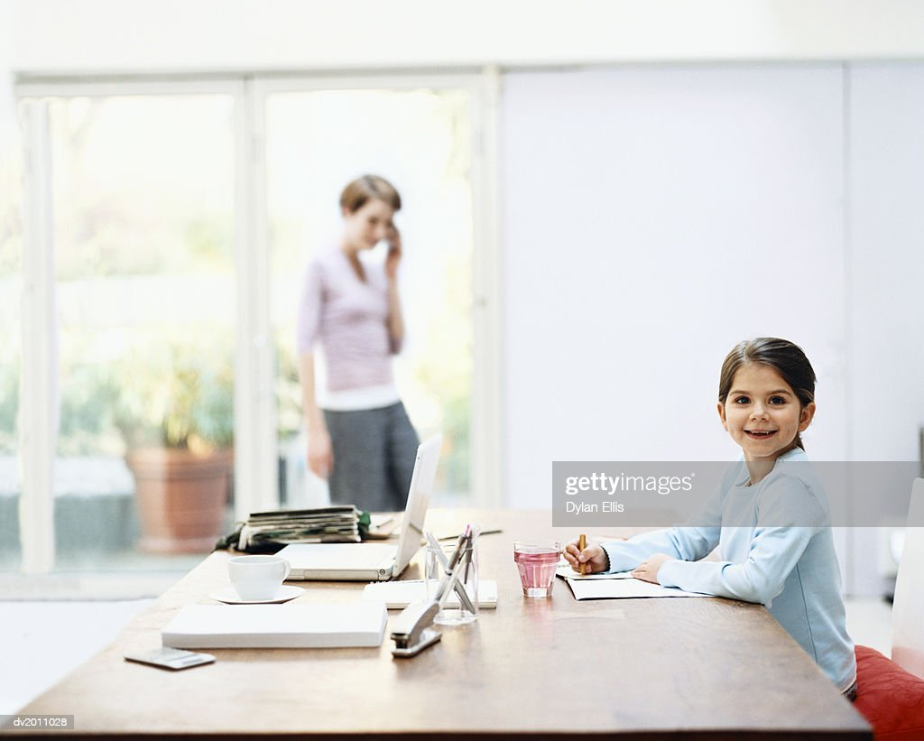 Young Girl Sits at a Table Drawing on a Notepad, Her Mother in the Background : Stock Photo
