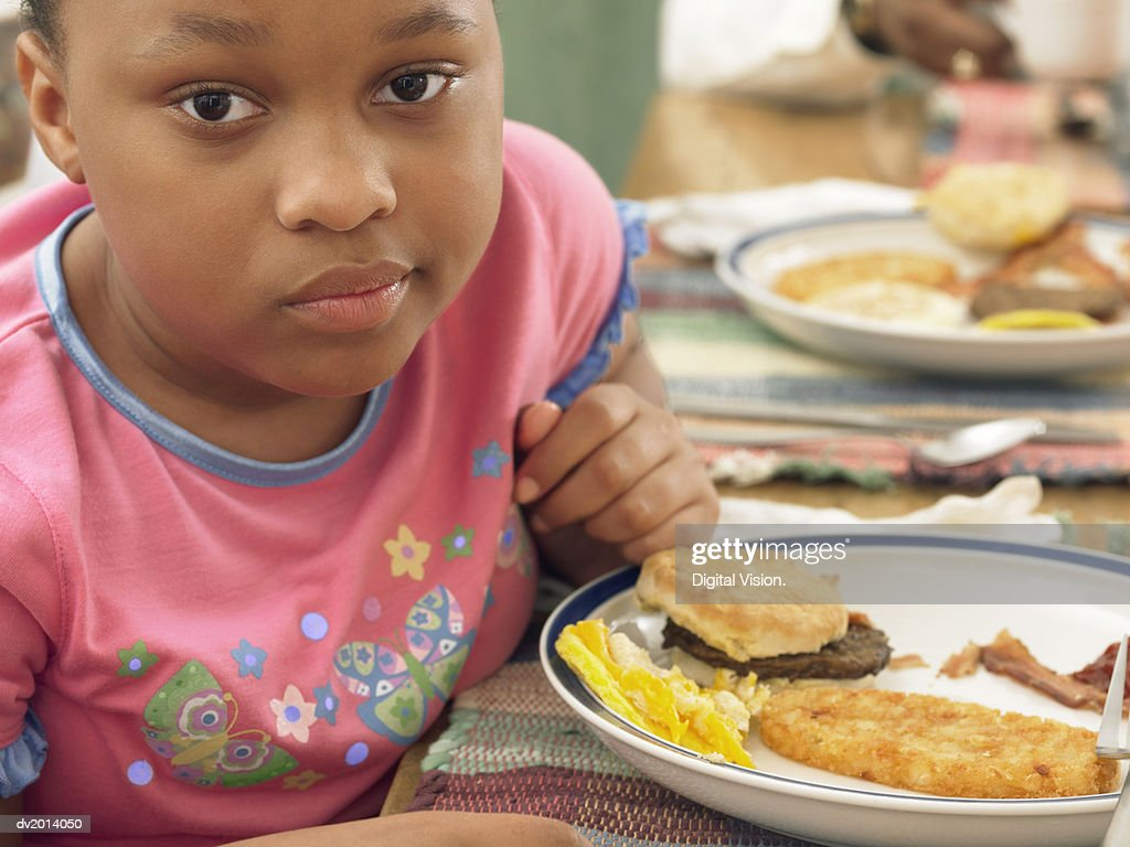 Young Girl Sits at a Table With a Plate of Fried Food for Breakfast, Looking Displeased : Stock Photo