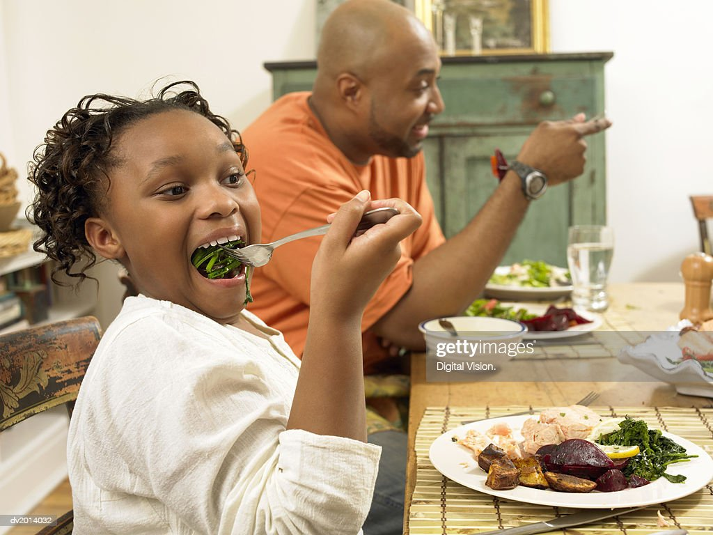 Young Girl Sits at a Table With Her Father, Eating Vegetables on a Fork : Stock Photo