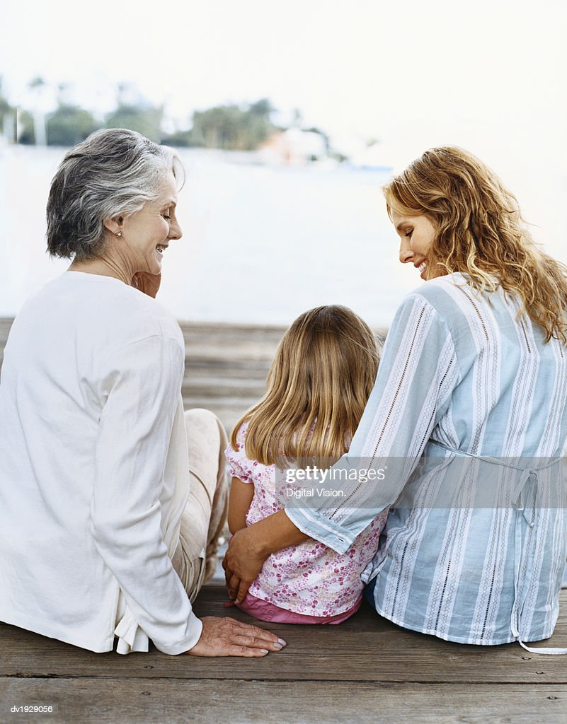 Young Girl Sits Between Her Mother and Grandmother on Outdoor Decking : Stock Photo