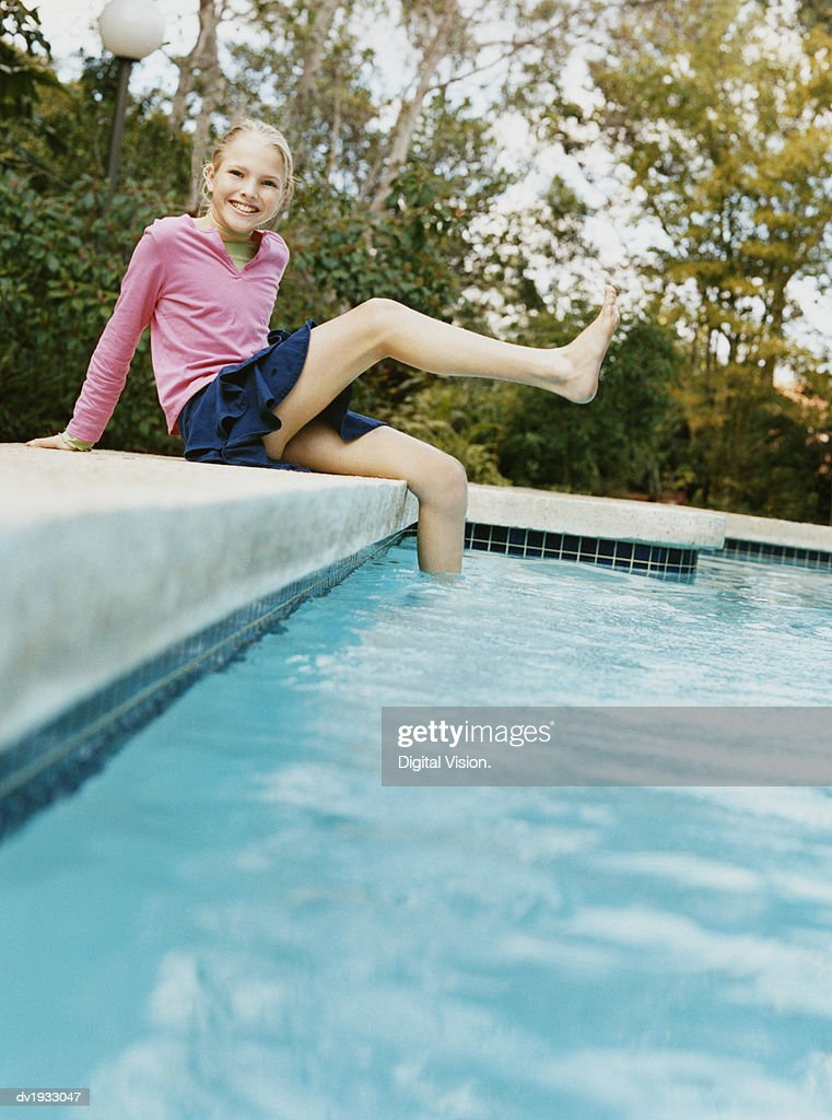 Young Girl Sits by a Swimming Pool, Kicking Her Leg in the Air : Stock Photo