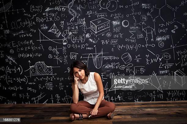young girl sits by mathematical chalkboarda - solo una donna giovane foto e immagini stock