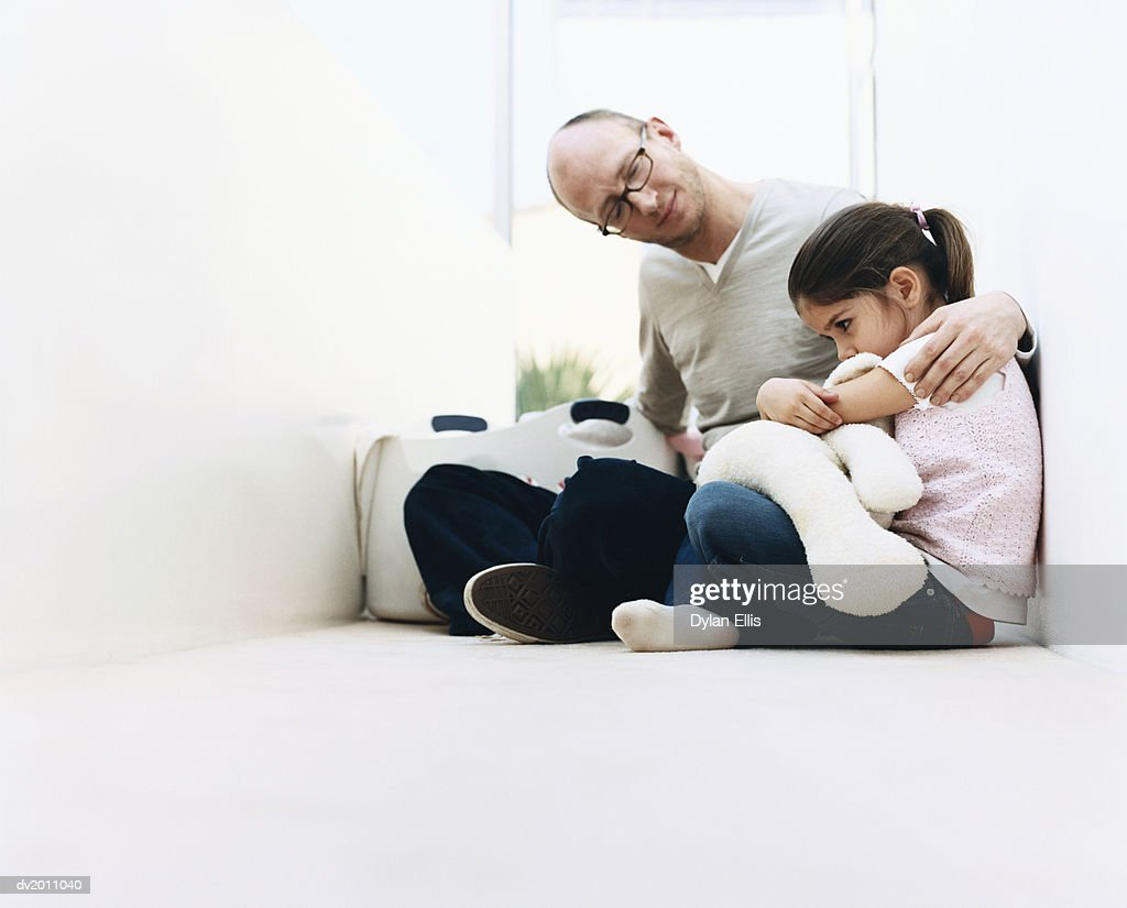 Young Girl Sits in a Corridor, Sulking, Her Father Comforting Her : Stock Photo