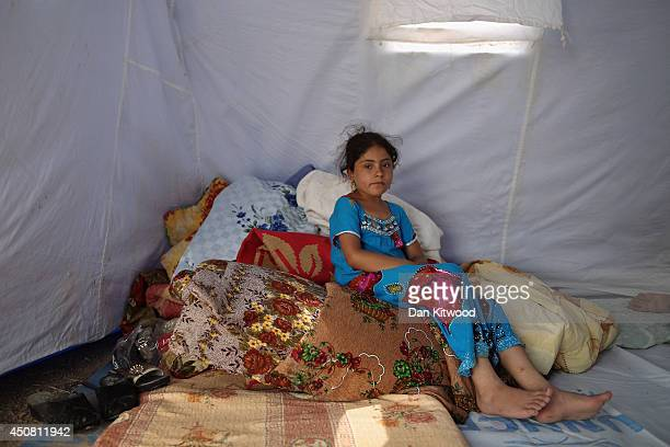 A young girl sits in a tent at a temporary displacement camp on June 13 2014 in Kalak Iraq Thousands of people have fled Iraq's second city of Mosul...