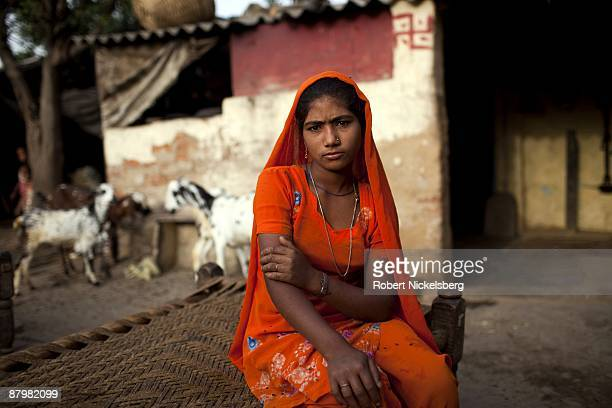 A young girl sits in a yard of a slum area near a newly dug roadway April 21 2009 where agricultural areas she and members of twelve families have...