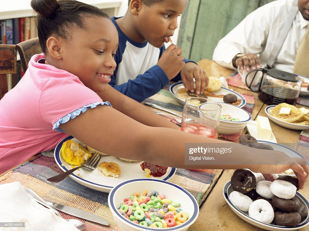Young Girl Sits Next to Her Brother at the Breakfast Table With a Plate of Fried Food, Picking up a Doughnut : Stock Photo
