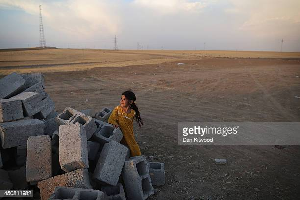 A young girl sits on a pile of concrete blocks at a temporary displacement camp on June 13 2014 in Kalak Iraq Thousands of people have fled Iraq's...