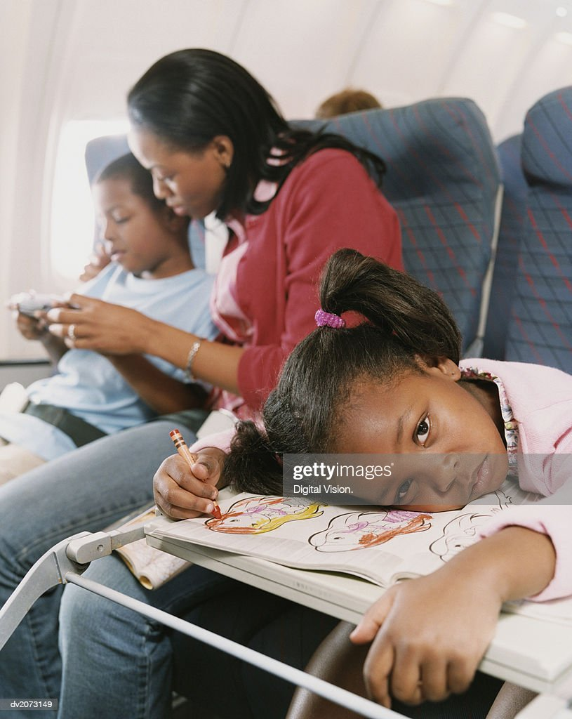 Young Girl Sits on a Plane Looking Bored, Her Mum and Brother in the Background : Stock Photo