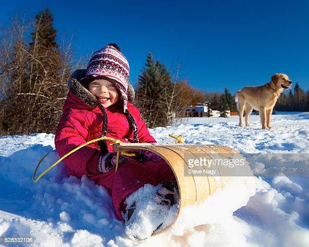 A young girl sits on a toboggan in the snow with a dog in the background; spruce grove alberta canada