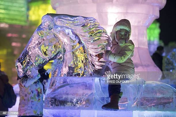 A young girl sits on an ice horse at the China Ice and Snow World at the 16th Harbin International Ice and Snow Festival in Harbin northeast China's...