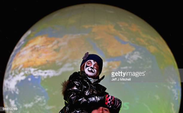 A young girl sits on her fathers shoulders at an evening demonstration on December 16 2009 in Copenhagen Denmark Hundreds of climate demonstrators...