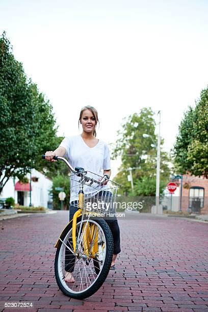 A young girl (13-15 years) sits on her yellow beach cruiser on a brick road in small town, Mississippi, USA