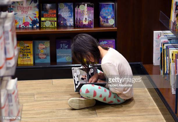 A young girl sits on the floor and reads as her mother shops in a bookstore located in the terminal at Denver International Airport in Denver Colorado