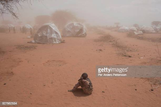 A young girl sits on the ground as a sandstorm hit the tents in the IFOR refugee camp on July 29 2011 outside Dadaab Kenya Hundreds of thousands of...