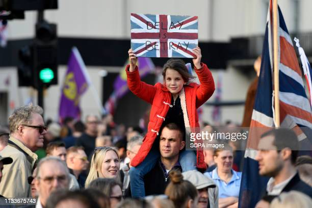 A young girl sits on the shoulder of a man carrying a placard that says Delay is betray during the Leave means leave rally in London A Leave means...