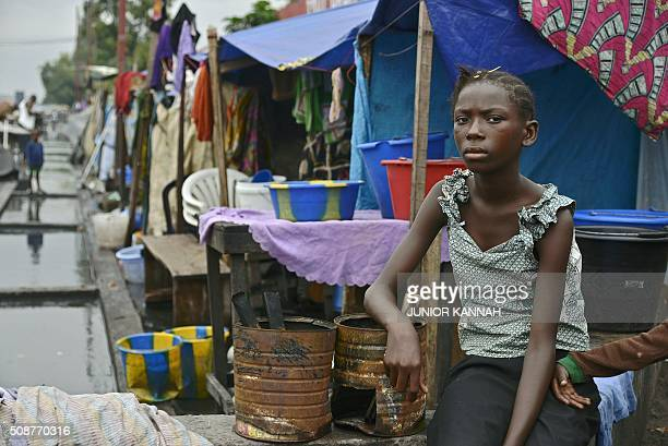 Young girl sits outside her flooded makeshift home in Kinshasa on February 5, 2016. For the last seven months 167 DR Congo families have lived in the...