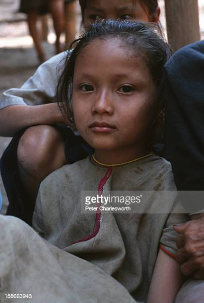 Young girl sits with friends near their wood and bamboo hut in a new Karen refugee camp north of the Thai town, Mae Sot. They are recent refugee...
