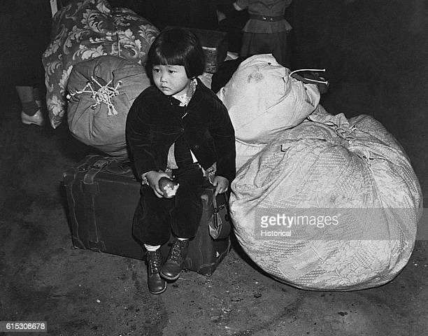 A young girl sits with the family baggage waiting for a bus that will eventually take her to an interment camp She along with some 112000 other...