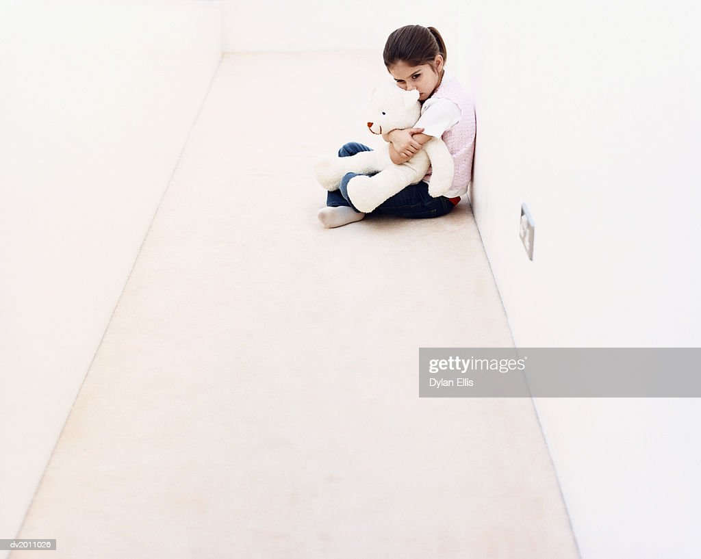 Young Girl Sitting Alone in a Corridor and Hugging a Cuddly Toy : Stock Photo