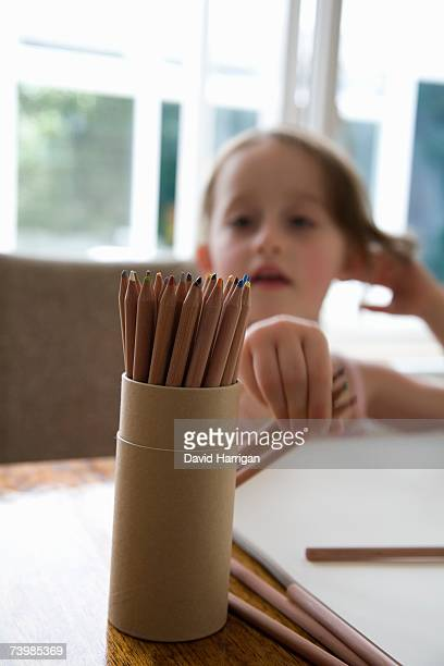 Young girl sitting at a table and reaching for colored pencils