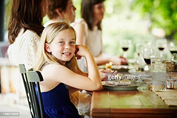 Young girl sitting at end of table with family