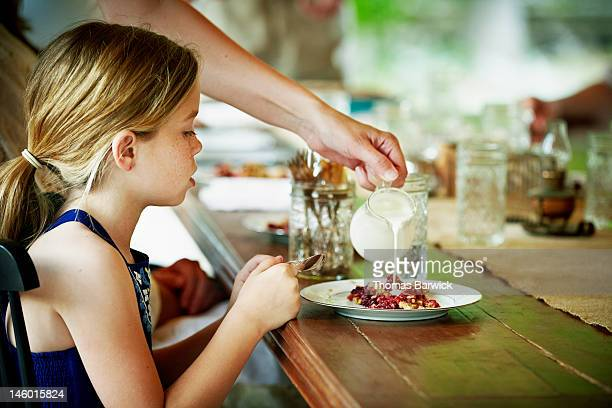 Young girl sitting at table waiting for dessert