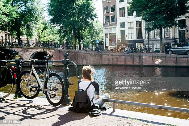 Young girl sitting at the canal in Amsterdam at sunset, Netherlands