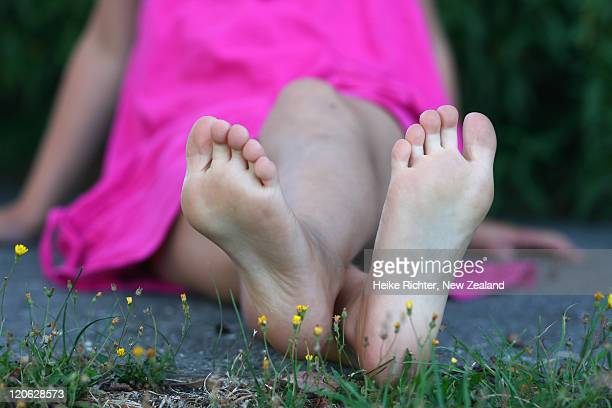young girl sitting bare feet - little girl soles stock photos and pictures