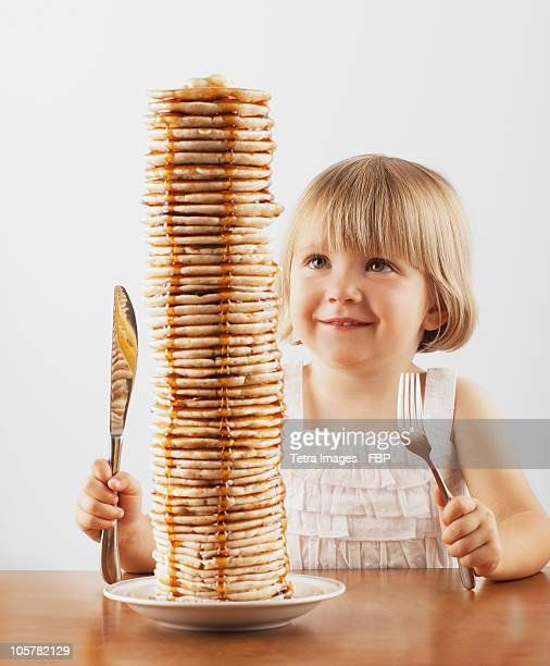 Young girl sitting behind a tall stack of pancakes