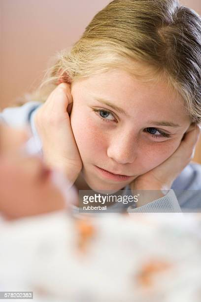 Young girl sitting by brother in hospital bed