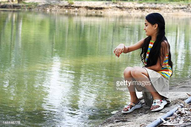 A young girl sitting by the lake